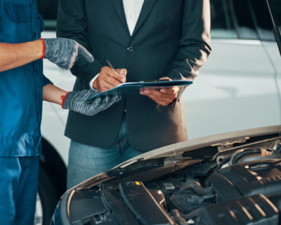 Close-up of auto technician in gloves pointing his client where he should to sign before repairing his car in workshop